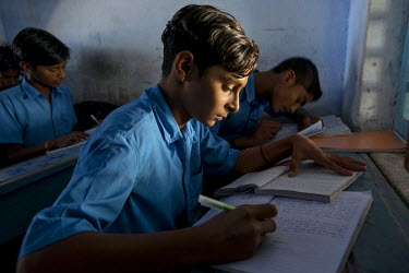 A boy dressed in blue studying at the Sanatan Seva Mandal school and orphanage (about half of the children are orphans) in Dwarka which provides an education for 435 students whose parents can't affor...