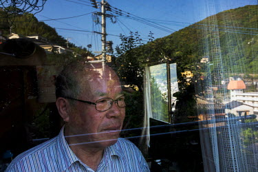 Shigemitsu Tanaka, Director of the A-Bomb Survivor's Council and himself an atomic bomb survivor, at his home, with the hills reflected in the window, in Nagasaki.