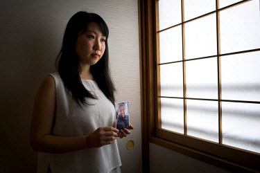 Kana Miyoshi, 22, poses for a portrait holding a photo of her grandmother Yoshie Miyoshi, 78, who survived the Hiroshima atom bomb, at her home in Hiroshima.