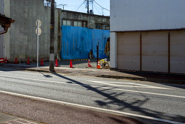 Clean up work on a street in the city of Namie. Following the 2011 Fukushima Daiichi nuclear disaster the town's 19,000 residents were evacuated and today it remains a ghost town.  On 11 March 2011 a...