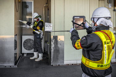 Clean up workers taking measurements of radioactivity levels in the town of Namie, eight kilometres from Fukushima nuclear plant.  On 11 March 2011 a magnitude 9 earthquake struck 130 km off the coast...