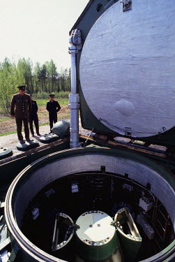 Russian nuclear forces officers look down into a missile silo showing an ICBM with the rocket head (opened) containing four MIRVs underneath, at a secret nuclear missile base.