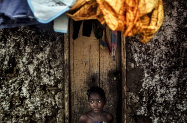 A girl who lost her parents to Ebola, stands outside her home in Njala Ngiema village.