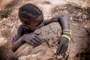 A shy young girl looks at visitors from behind a tree stump.