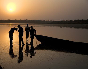 Fishermen wait beside their boat at sunrise for the tide to rise in the River Buba.