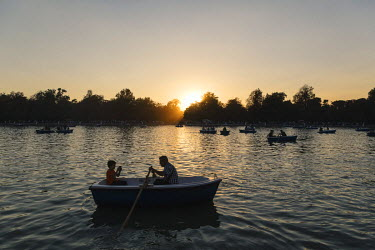A father and son enjoy the last of the evening light on the boating lake in Parque del Retiro.
