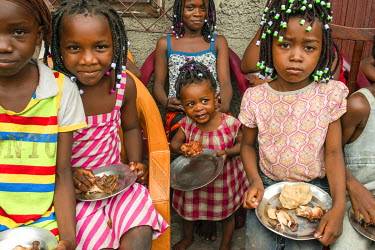Children eating a meal of chicken and a staple made of manioc (yuca, cassava).