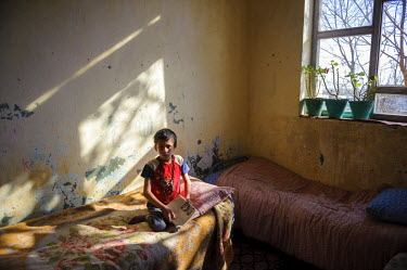 A boy sits on a bed in the light of a large window at the Kabul Orphanage.