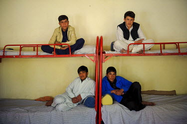 Boys sit on their beds in an orphanage.