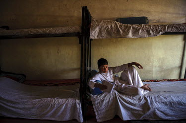 A boy revising his school lessons in his bed at an orphanage.
