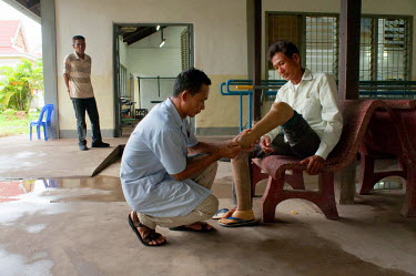 Tith Pao (45), who lost a leg when he stepped on a landmine, has a new foot fitted by prosthetist Song, Mom at Battambang Physical Rehabilitation Centre, who has known Pao since 1999 and has fitted hi...