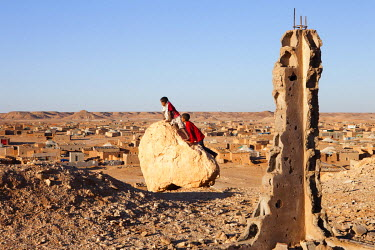 Children climb a boulder overlooking Laayoune refugee camp, one of five refugee camps where refugees from Western Sahara have been housed by the Algerian Government since 1975.