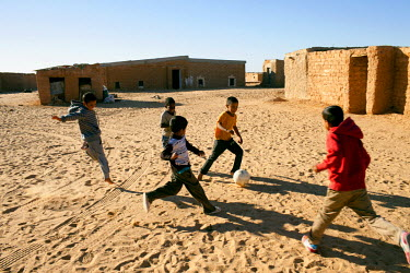 Children play football at Aousserd refugee camp, one of five refugee camps where refugees from Western Sahara have been housed by the Algerian Government since 1975.