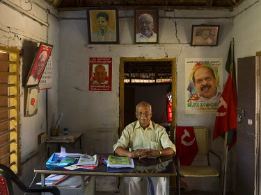 N.P. Vidyanandan, secretary of Punnapra South local committee office of the Communist Party of India. Behind him, beside the flag, is a portrait of G. Sudhakaran, minister for public works in the Kera...