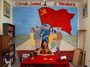 Party activist Laura Vari from the Lenci circle of the Communist Refoundation Party (PRC) sits in an office in front of a mural featuring the Hammer and Sickle flag.