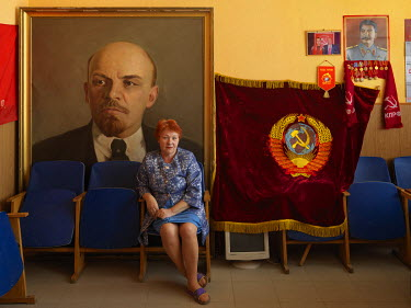 Olga Volnina, First Secretary in the Torzhok office of the Communist Party of the Russian Federation, sits in front of a large portrait of Vladimir Ilyich Lenin in the party's office. On the wall behi...