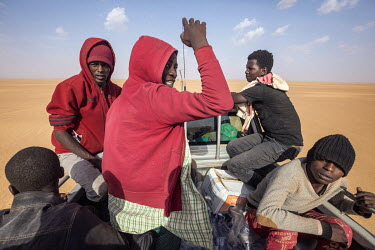 Members of a group of migrants who were left in the desert between Arlit and Assamaka on the Algerian border by their people smuggler after the group was robbed twice by local bandits and two of the w...