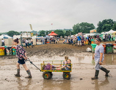 Two festival goers drag their kids through the mud at the 2016 Glastonbury Festival.