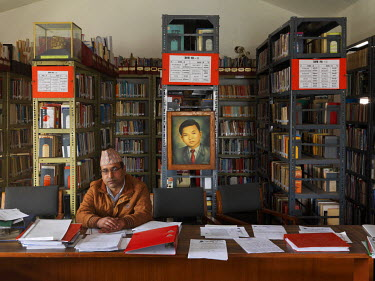Librarian R.C. Boharaat in the headquarters of the Communist Party of Nepal (Unified Marxist�Leninist), also known as CPN�UML or CPN (UML).    The portrait behind him is of Ratna Kumar Bantawa,...