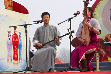 Traditional storytellers, playing Chinese musical instruments, performs at the Ma Jie folk festival.   For centuries farmers in Henan have gathered during Chinese New Year in the region's wheat fields...