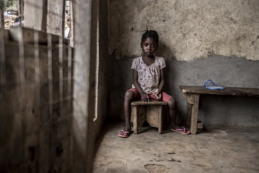 Five year old Adama, who was orphaned during the 2017 mudslide in Regnet, sits in a corner in a house rented by her older sister. Adama was rescued from the mudslide by her brother in law.