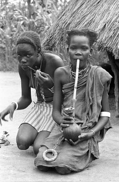 Two Anuak girls, one of whom smokes a pipe made from a gourd.
