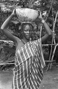 An Anuak woman carries a gourd on her head.
