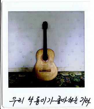 A Polaroid of a guitar with Kim Myong Hui's handwritten note: 'Hak Ryong's favorite guitar.' Kim Myong Hui's husband received this guitar as a reward from a farm about 15 years ago. Her son Hak Ryong...