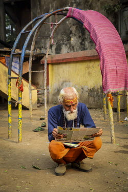 A man witha Tilaka on his forehead squats while reading a newspaper.