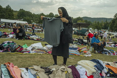 An elderly woman examines a second hand shirt at a stall selling items imported from western Europe and sold for between one and five Euros, at a flee market attached to a Roma festival celebrating th...