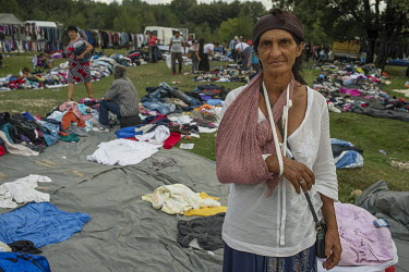 A woman with a broken arm selling second hand clothes and shoes, imported from Western Europe and sold for between one and five Euros, at a flee market attached to a Roma festival celebrating the Birt...