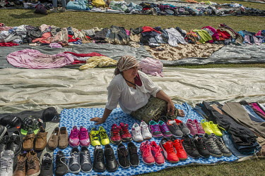 A woman selling second hand clothes and shoes, imported from Western Europe, are sold for between one and five Euros at a flee market attached to a Roma festival celebrating the Birth of the Virgin Ma...