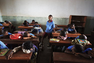 A student stands in the classroom as he is in charge and must keep the class quiet while the teacher is away at the Notre Dame orphanage and school.