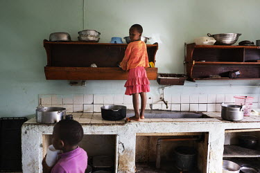 Young girls cleaning and pots and dishes after lunch in the kitchen at the Notre Dame orphanage and school.