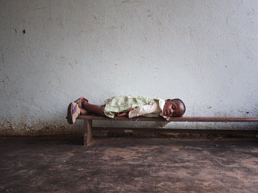 After lunch, a boy falls a sleep on a bench outside the canteen at the Notre Dame orphanage and school.