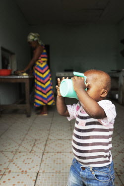 A child drinking a cup of water at the entrance to the kitchen of the orphanage Notre Dame orphanage and school.