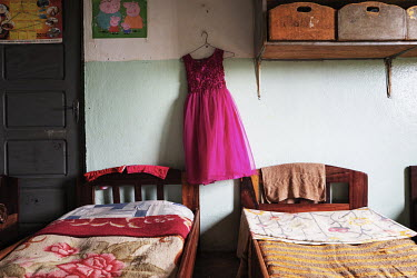 A dress hangs by a bed at the girl's dormitory in the Notre Dame orphanage and school.