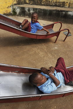 Two boys play on the slides after the lesson in the playground at the orphange Notre Dame orphanage and school.
