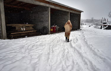 A Pakistani migrant walks in the snow beside an unfinished garage where he is squatting with other Pakistani migrants. They are all hoping to get to western Europe. For a few months they were living i...