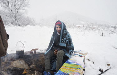 A migrant from Pakistan Qasim (17) sits by a fire outside an unfinished garage where he is squatting with other Pakistani migrants. They are all hoping to get to western Europe. For a few months they...