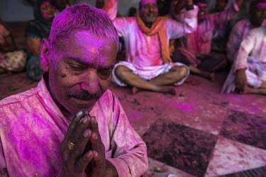 A man, smeared with coloured powder during the Lathmar Holi spring festival, praying.