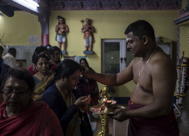 A Tamil priest blesses Hindu devotees in a temple in Lalmatie.