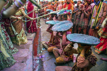 Women 'beat' men with sticks during the Lathmar Holi spring festival. During the festival men from the nearby town of Barsana raid Nandgaon where they are assaulted with coloured water sprayed from ro...