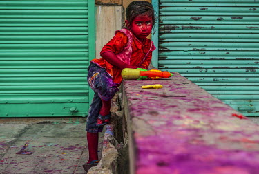 A child smeared with coloured powder during the Lathmar Holi spring festival.