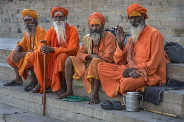 Sadhus (Hindu holy men) sitting on th eghats beside the Ganages River.