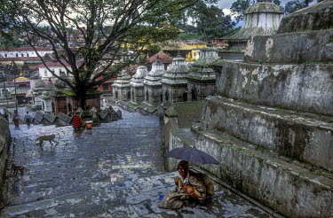 A man squats beside Chedis above the Pashupati Temple, where Hindu cremations take place.