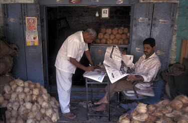 Men selling coconuts red newspapers while they wait for customers.