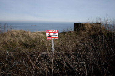 A sign, near a German concrete bunker from World War Two, warns of the danger from falling rocks on the cliffs above Gold Beach, one of the five landing sites along the Normandy coast where allied for...