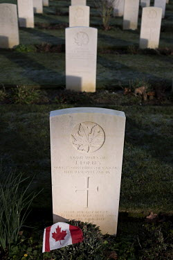 A headstone and a flag mark the grave of a soldier killed during Operation Overlord, the invasion of western Europe, in the Beny-sur-Mer Canadian War Cemetery.