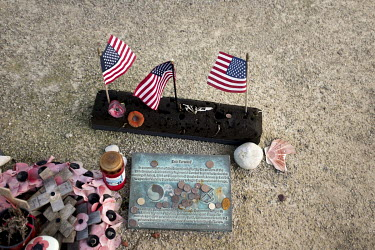 American flags and coins left beside 'Ever Forward', a statue of two American soldiers, above Omaha Beach one of the five landing sites along the Normandy coast where allied forces landed on D-Day, 6...